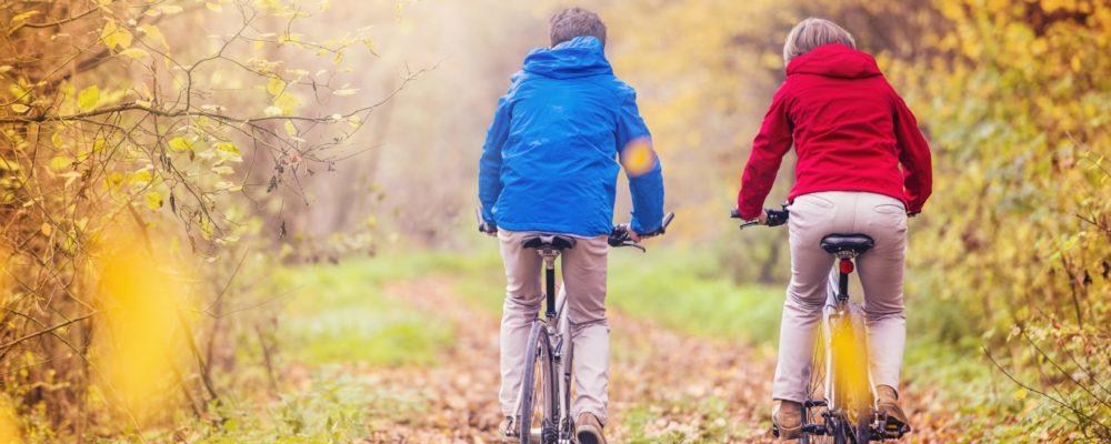 active-seniors-riding-bike-PUR7DFJ