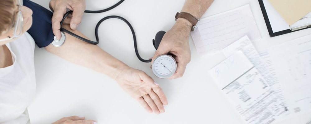 doctor-measuring-patients-blood-pressure-PQATB85