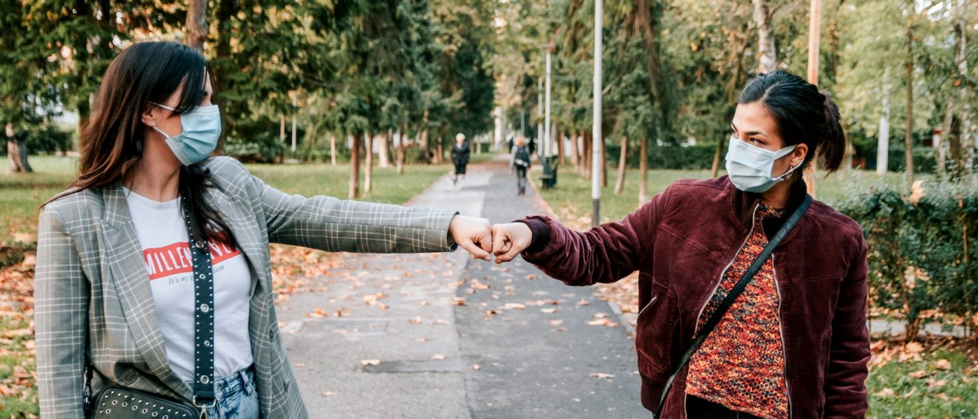 friends-in-city-fist-bump-greeting-in-the-park-cor-L7HPQ52