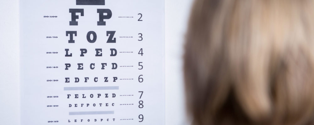 optometrist looking at eye chart in ophthalmology clinic