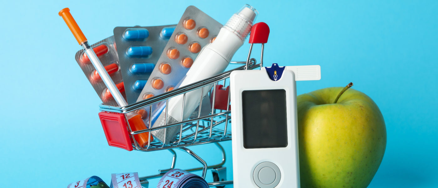 Shopping cart with diabetes accessories on blue background
