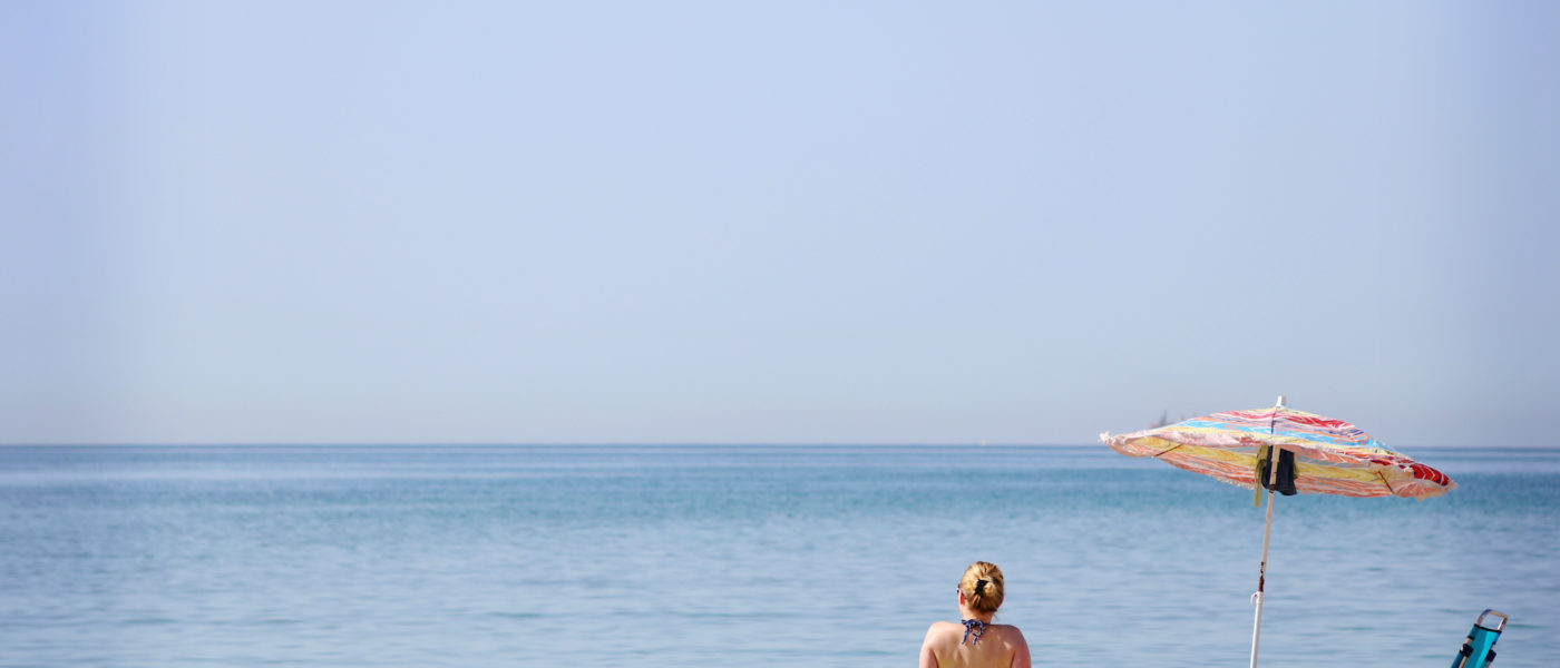 woman-sitting-at-the-beach-watching-the-sea-VDWSVQ3