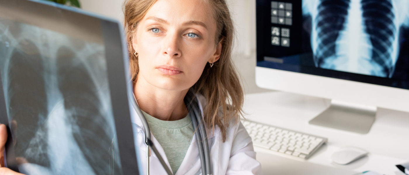 Young serious female radiologist in whitecoat pointing at x-ray image of patient lungs while sitting against workplace with computer monitor
